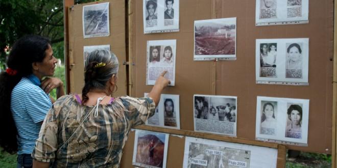 Amanda Araceli y Vilma Elizabeth Rivera observan las fotografías de las víctimas en la tragedia de Monte Bello, en 1982. La conmemoración fue organizada por la Comunidad Pueblo de Dios. Foto Diario Co Latino / Jorge Rivera.