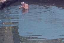 Un lugareño se baña en una pileta que se llena con agua del Río San Antonio.