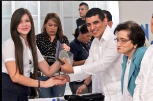 El Viceministro de Educación, Francisco Castaneda, acompañado de la exministra de Salud, María Isabeil Rodríguez, entregan un reconocimiento a una estudiante por su alta calificación en la PAES.  Foto Diario Co Latino.