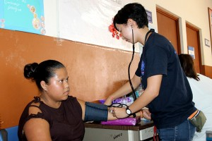 Yuki Kuniyoshi, Voluntaria de JICA, toma la presión de la paciente de Ana Ruth Tadeo, originaria de Ahuachapán.  Foto Diario Co Latino / Jorge Rivera.